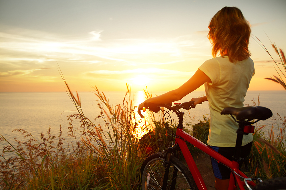 Person standing next to a bike watching the sun set