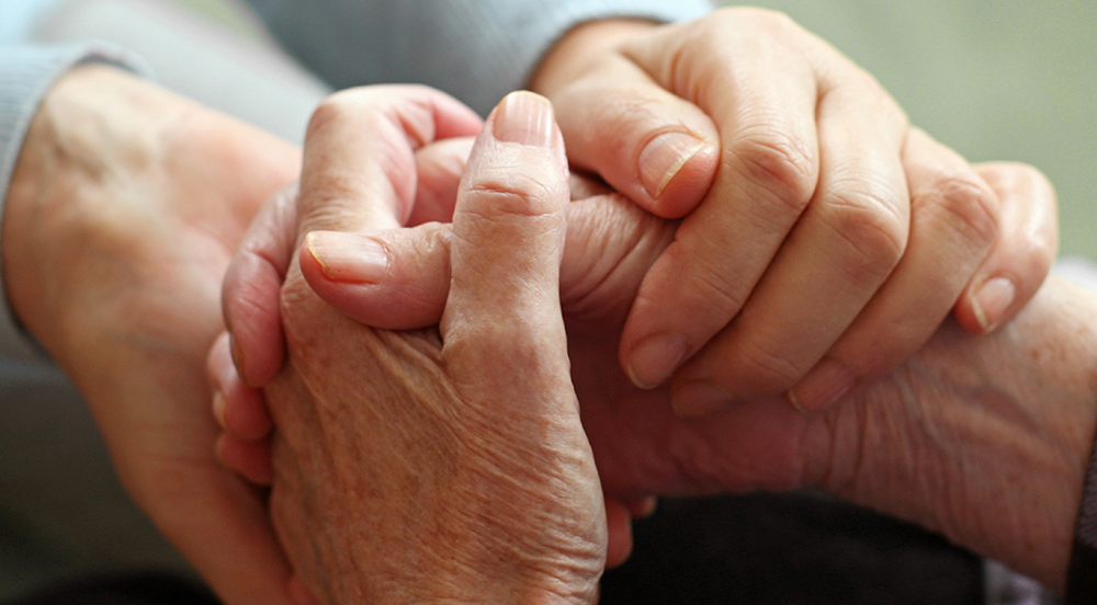 24 Hour Crisis image Elderly person holding hands with another person